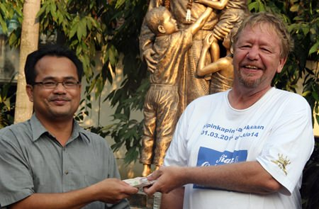 Khun Pae, Manager of the Drop-In Center, accepts the donation from Gizmo.
