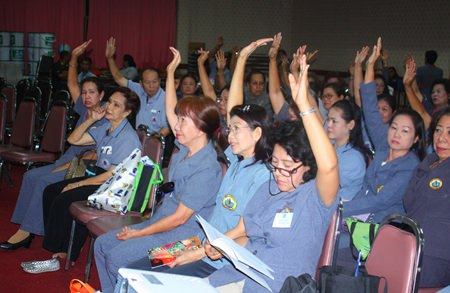 Pattaya Public health volunteers members raise their hands to approve Suphin Ruangrung as the next president of Pattaya Public Health Volunteers.