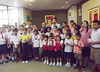 Mayor Itthiphol Kunplome (back, center) and city officials take a group photo with students who received mobile phones.