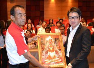 Jeerasak Hengsawat (left), president of the Puttaisong Sub-district in Buriram, presents an upcountry souvenir to Pattaya City Councilman Rattanachai Suthidechanai (right).