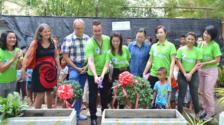 Nigel Quennell and Praichit Jetpai cut the ribbon to officially launch the project, whilst Maggie Travis (2nd left), Russell Iffland (3rd left), Sister Kanyanee Tuanrussmee (4th right), and Nicha Loychun (2nd right), along with YWCA members, Fountain of Life staff and children cheer them on.