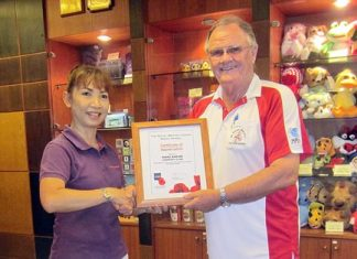 Derek Brook (right), on behalf of the Royal British Legion Thailand, presents a certificate of appreciation to the staff at Khao Kheow Country Club.