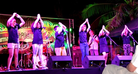 Students perform international choral music on stage.