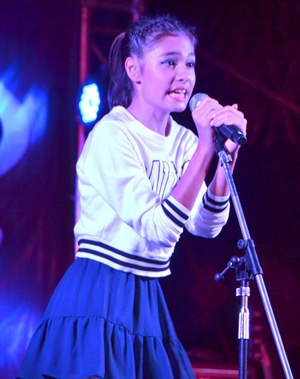 A budding, young singer demonstrates her vocal talents to the audience.