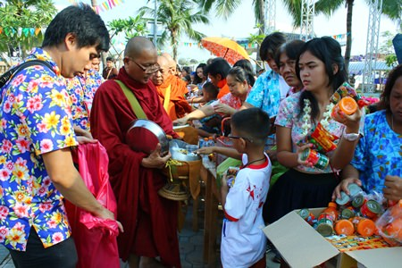 The quieter side of Songkran - Citizens present alms to monks, offering rice and dried food at Lan Po Public Park.
