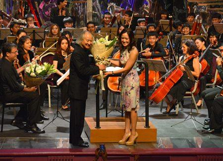 The assistant managing director of Tiffany's Pattaya, Alisa Phanthusak, presents flowers to Maestro Hikotaro Yazaki.
