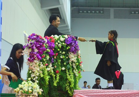 Mayor Itthiphol Kunplome presents a graduation certificate to one of over 2,000 students on March 18 at Pattaya's at Indoor Stadium.