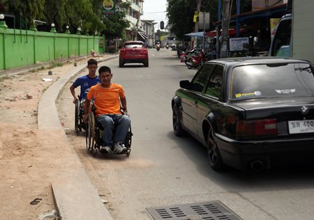 Thongrob Taomafuang and Atthaporn Pansena travel alongside the yet to be completed designated wheelchair path.