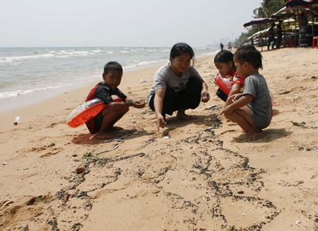 Mother Apaporn Somjai, 22, brought her children to play in the ocean but quickly pulled them out when she noticed the oil.