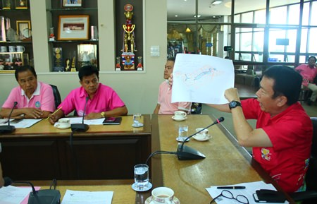 Banglamung District Chief Sakchai Taengho holds up a map showing the trespass area that authorities need to work on.