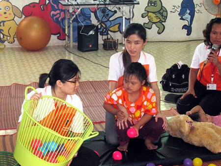 Karuna Piromtan (right, with microphone), seen here with two teachers and an autistic child, is a supervisor of therapy education from the Ministry of Education in Chonburi.