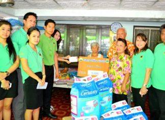 Nanatnanthanan Phithaksanantakul, president of the Helping the Disabled project, presents cash to Grandmother Bunkhoi Niemkarn.