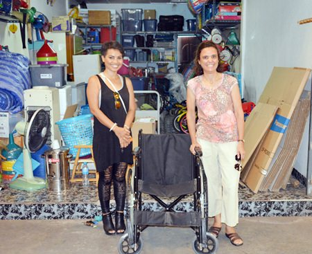 """Margaret Grainger from the Hand to Hand Foundation (right) donates a surplus wheelchair to Saisamorn """"Yui"""" Pithak (left) for her 94-year-old grandmother in Khon Kaen."""