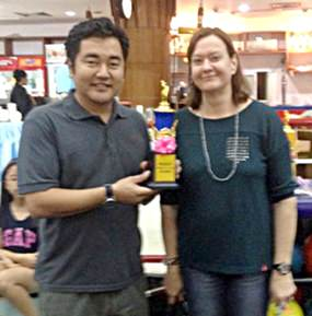 Edson Uehara (left) is presented with the top scoring adult prize by PILC President Helle Rantsen.