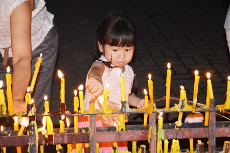 N'Imjai learns how to place candles in the prayer area after completing her 3 Wien Thien rounds.