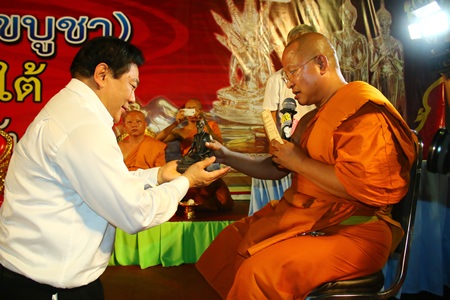 Chanyuth Hengtrakul (left), advisor to the Ministry of Education, accepts a Dr. Jivaka Kumar Bhacca statuette from Phra Punya Rattanaporn, abbot of Wat Chaimongkol Phra Aaramluang.