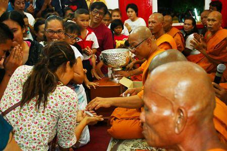 Citizens receive gifts from Phra Pladsuttassana Suthammo, abbot of Wat Bunyakanjanaram (middle).