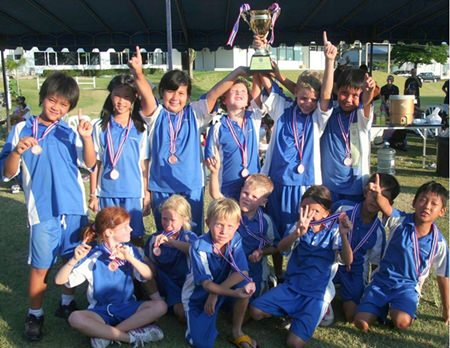 St. Andrews Year 5 football teams celebrate winning a medal.