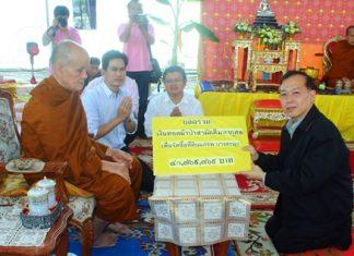 Phra Khru Vibun Thammakit, former abbot of Wat Chonglom, presents over 41 million baht to Visit Tangnapakorn, ombudsman of the Ministry of Public Health, representing Banglamung Hospital.