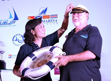 Supatra Angkavinijwong, Deputy Managing Director of Ocean Property Co., Ltd., (left) bestows an admiral's cap on Bill Gasson to mark the TOG Regatta founder's final year in charge of the event. (Photo/TOG Regatta)