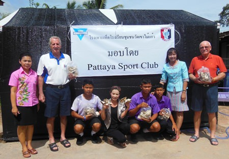 Members of the YWCA and Pattaya Sports Club pose with students and teachers in front of one of the many farms.