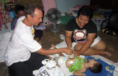 (L to R) The phlegm suction machine donated by the Graham and Jay, the gastrostomy wound site on the girl, and Woody handing the cash from Jim to the mother.