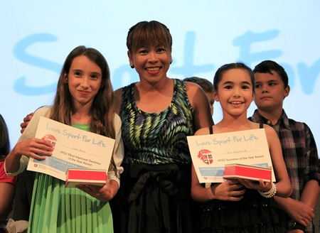 PE Teacher Miss Meena hands out certificates to two more deserving students.