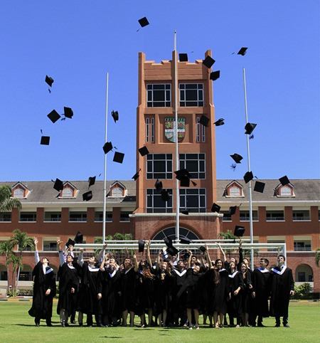 In true graduation tradition, students throw their mortar boards high into the air in celebration.