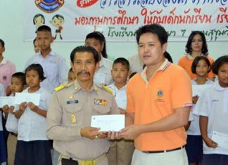 Manas Kongwattana (left), principal of Pattaya School No. 7, receives 20 scholarships, amounting to 20,000 baht, for the selected students from years 1-6 of the school.