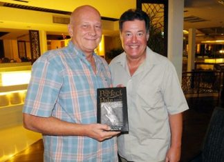 """Past President Jan Abbink (left) receives a signed copy of """"The Perfect Pair"""" from author David C Holroyd (right)."""