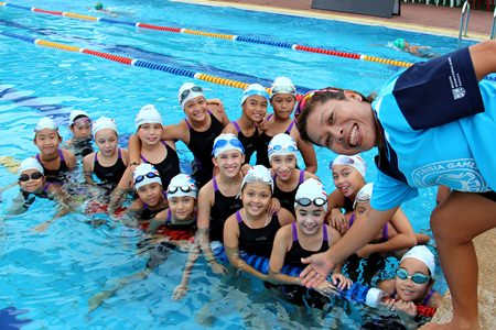 PE teacher Miss Meena poses with her young swimming team.