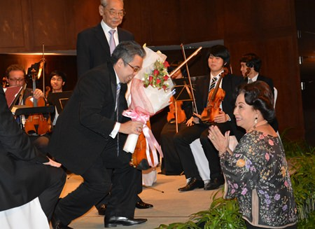Siam Bayshore owner Kamala Sukosol (right) presents flowers of appreciation to soloist Siripong Tiptan while conductor H.E. Admiral M.L. Usni Pramoj looks on.