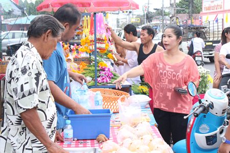 Local people purchase food to donate to the monks at Wat Suttawas.