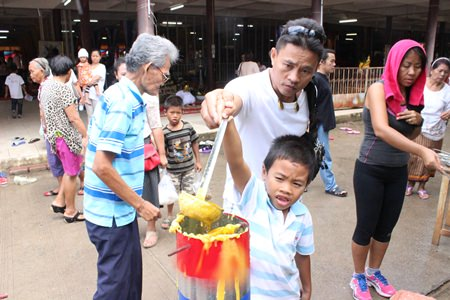 Father & son cast candles together to increase brightness in their lives and to instill the importance of Thai traditions in the next generation at Wat Bunsamphan.