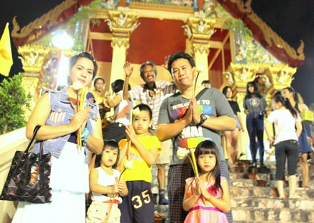 At Wat Phothisamphan, families came for the 'wien thien' ceremony on this important Buddhism day.