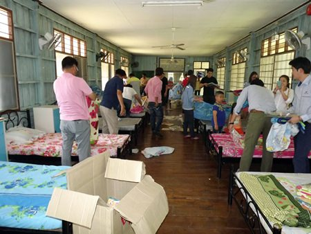 After donating bedding and sporting goods to the Banglamung Home for Boys, members of the South Korean Thai Aridang Association help change bed sheets and clean the fans in the dormitory.