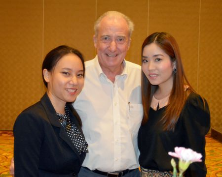 Dr. Iain Corness (center, wearing boring white shirt) poses for a photo with young ladies Chanamon Watetip (left), Assistant Manager - Sales of the Dusit Thani Pattaya and Nattawan Thammarak (right), Manger - Sales of the Dusit Thani Pattaya.