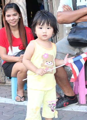 A little child waves the Thai flag.