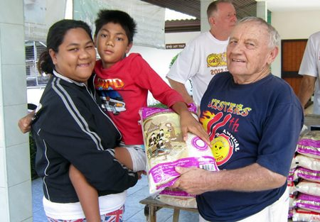 Nathawat, shown here with Bernie and Erle during the monthly rice distribution, had out grown his wheelchair, compelling his mother to try and carry him around.