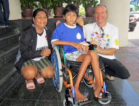 Lewis Underwood (right) presents a new wheelchair to Nathawat and his mother in front of Nongprue City Hall.