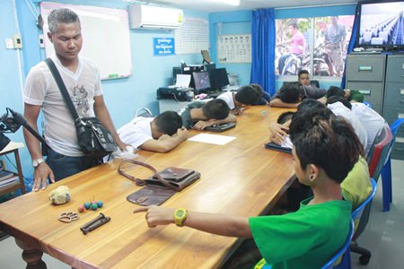 One of eighteen teenagers taken into custody for brawling in Sattahip points to weapons intended for use in the skirmish.