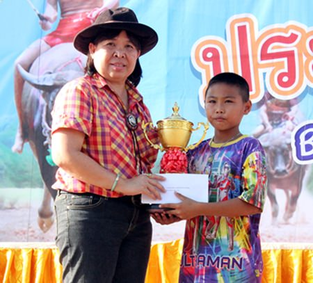 Anyamanee Khumjan, permanent secretary of Nongprue municipality (left) hands the trophy and 6,000 prize money to 14-year old N' Wai Ban Mabphai, the winner of the 'Big' level.