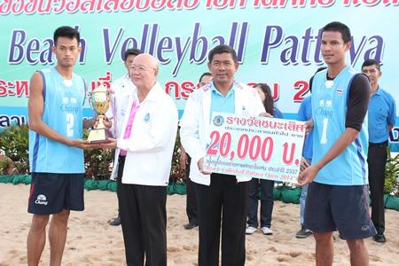 Pattaya Deputy Mayor Wattana Chantanawaranon (2nd left) presents the male winners' trophy to the victorious Navy 1 team.