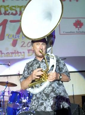 Multi-instrumentalist Paul Rosenberg heralds the start of the Grand Raffle.