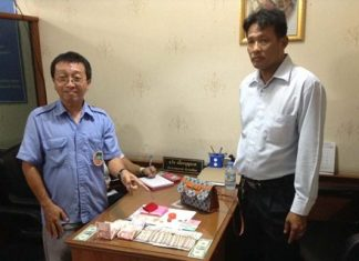 Korapat Teerapripruek (left), driver of Pattaya Transportation Cooperative bus No. 83, turns the lost handbag and its contents in to cooperative President Thawat Puagboonnak (right) at headquarters where it was later claimed by its rightful owner.