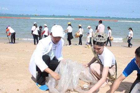 Mayor Itthiphol Kunplome and Polly Punnika, still wearing her tiara from her earning 1st runner-up at the Miss Earth of Water pageant, help Pattaya-area residents pick up trash from Pattaya Beach.