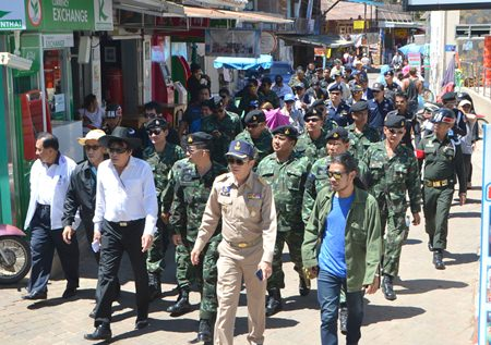 An entourage of government officials, military and local police make their way to inspect Koh Larn's beaches.