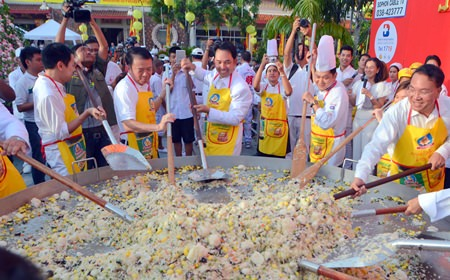 """It takes a lot of hands, and some big skillets, to feed 5,000 people, but organizers of the Pattaya Vegetarian Festival had it covered again this year in Naklua.  Shown here, Mayor Itthiphol Kunplome and Banglamung District Chief Sakchai Taengho help the """"master chefs"""" create this batch of delicious heavenly rice. The festival comes to a conclusion today, Oct. 3."""