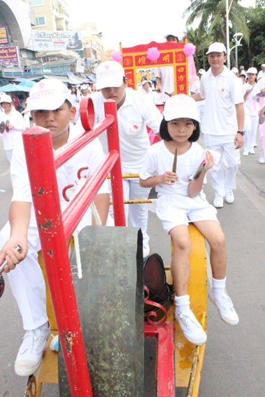 A young boy has been put in charge of banging the gong to announce the presence of the parade through town.