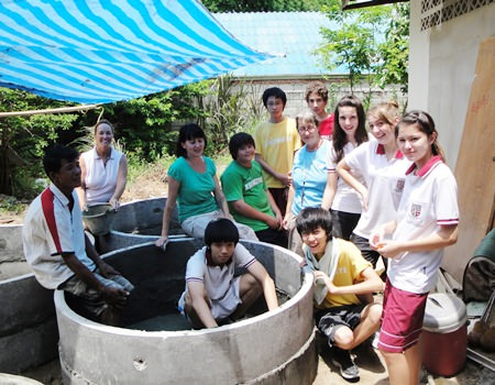 Students from Regents International School with the WWM team working to build fish tanks to help set up small businesses for families with handicapped members.